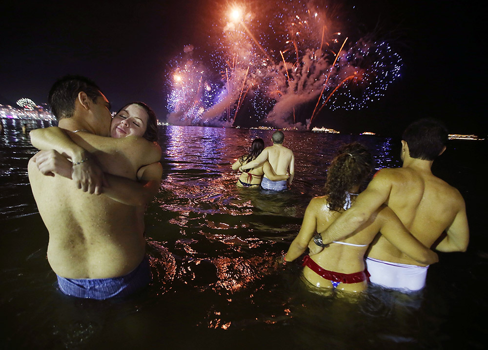 RIO DE JANEIRO, BRAZIL - JANUARY 01:  Couple embrace while watching fireworks explode minutes after midnight along Copacabana Beach during New Year's celebrations on January 1, 2014 in Rio de Janeiro, Brazil. More than two million were expected to attend the celebrations at Copacabana to ring in 2014. Brazil is gearing up to host the 2014 FIFA World Cup and the Rio 2016 Olympic Games.  (Photo by Mario Tama/Getty Images)