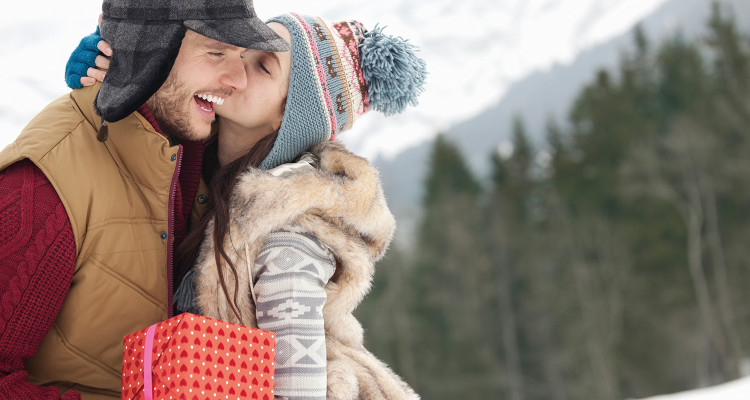 Happy couple with Christmas gift kissing in snowy field
