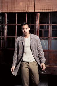 長版風衣外套、白色圓領毛衣、卡其色休閒褲_價格電洽 by Alfred Dunhill。