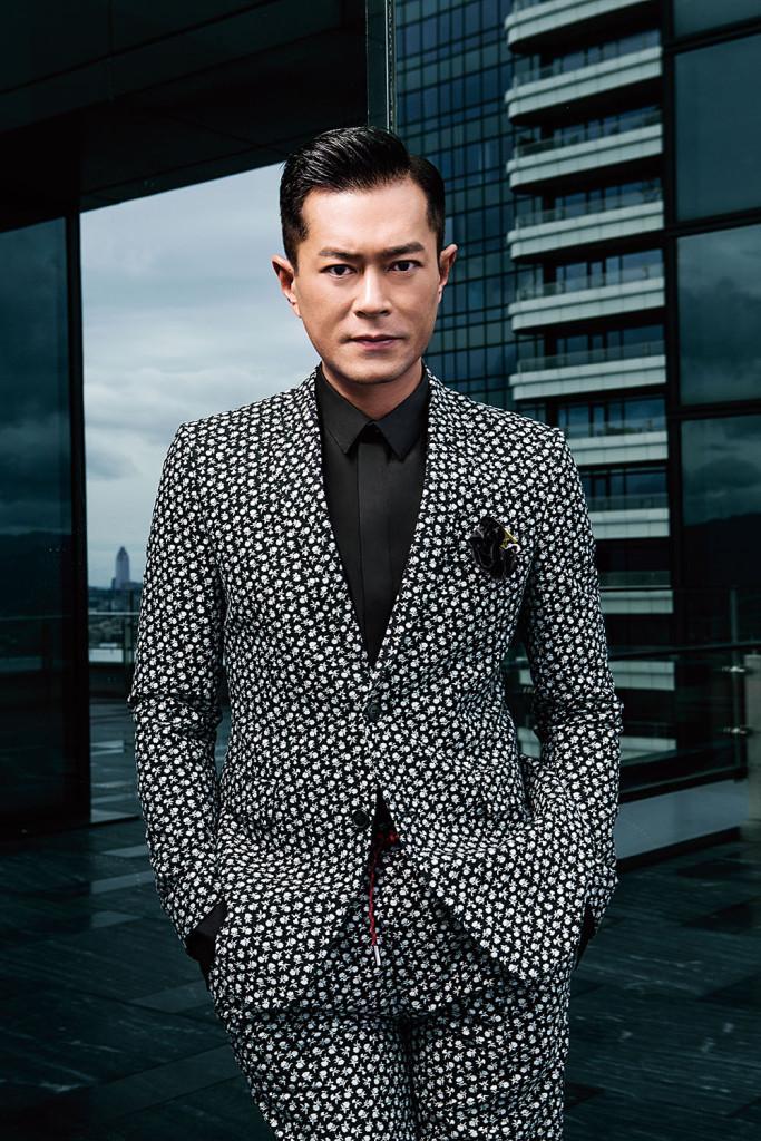 玫瑰花西裝外套_$79,000、黑色襯衫_$26,000、玫瑰花抽繩長褲_$35,000、黑色玫瑰花絲質胸針_$22,000 by Dior Homme。
